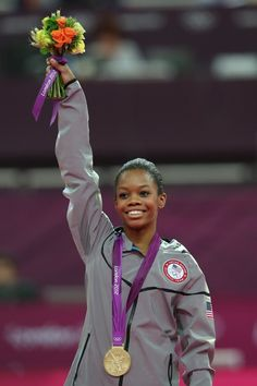 Gabrielle Douglas of the United States celebrates on the podium after winning the gold medal in the Artistic Gymnastics Women's Individual All-Around final! GOLD BABY!