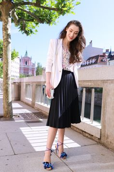 Fashion blogger Veronika Lipar of Brunette From Wall Street sharing how to wear black vintage midi plissé skirt, blue Tropicana tasseled beaded sandals from Aquazzura, floral top, and white blazer for a chic summer look