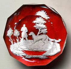 "Baccarat Glasshouse, ""The Hunter and His Dog"" sulphide paperweight on a ruby flash ground, ca. 1840. Currier Collections Online."