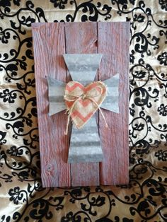 """This Country chic wall decoration measures 18"""" x 10"""". It is crafted from reclaimed lumber and hand painted. A rustic corrugated tin cross with a"""