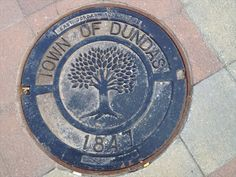 This manhole cover memorializes Dundas's incorporation in 1847. It also depicts the Chinquapin Oak tree, a famous 200 year old oak just down the street. The cover sits in Memorial Square and was made by East Jordan Iron Works.