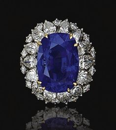 SAPPHIRE AND DIAMOND RING, OSCAR HEYMAN & BROTHERS.  Claw-set with a cushion-shaped sapphire weighing 17.84 carats, within a line of pear-shaped diamonds, further decorated with brilliant-cut stones, mounted in yellow gold and platinum