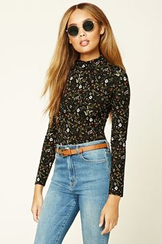 A knit floral print bodysuit with a mock neckline, long sleeves, and a snap-buttoned closure.