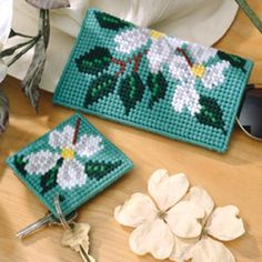 "Welcome nature's floral symphony into your life with these perennial favorites. Dogwood blossoms cover our eyeglass case and matching key ring with beauty that blooms year-round. The designs are stitched using worsted weight yarn and 7 mesh plastic canvas. <p><strong>Number of Designs:</strong> 2 - Key Ring & Eyeglass Case </p><p><strong>Approximate Design </p><p><strong>Size:</strong></strong> Key Ring 3-1/4""w x 3-1/4""h and Eyeglass Case 3-3/4""w x 6-1/2""h"