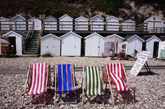 Striped deckchairs and bathing huts on pebbled Beer beach, Devon.