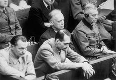 Rudolf Hess apoya sus manos sobre el banco de los acusados. Juanto a él: Joachim von Ribbentrop, Wilhelm Keitel, y Hermann Goering