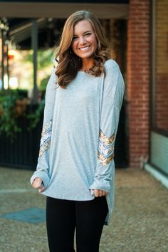 "You gotta know that this light gray tunic is a must-have for the season! The solid top is adorned with sequined arrows on the sleeves in silver and gold for a cherry, seasonal look! Bra-friendly! Material has generous amount of stretch. Sara is wearing the small. Length from shoulder to hem: S- 31""; M- 32""; L- 33""; XL- 34""."