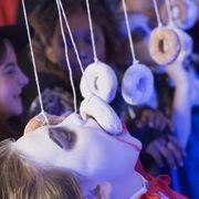 Fun Halloween Game Ideas | 4 players at a time, 1st person to finish doughnut wins, can also be 1st person to eat the most of their doughnut in 1 min. Wins