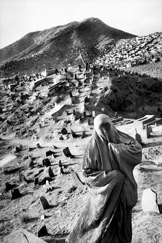 Kabul, Afghanistan  - A woman in Burqah, the full islamic veil, has come to pay respect to the dead at the Shi'ite shrine of Sakhi, January 2001