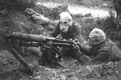 World War I machine gunners wearing primitive gas masks.