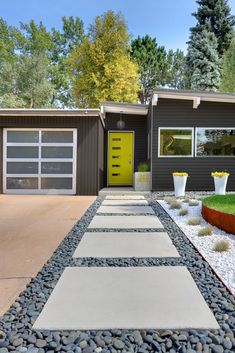 Generous concrete pavers lead to the entrance. The home's angles are typical of the midcentury homes in the neighborhood.
