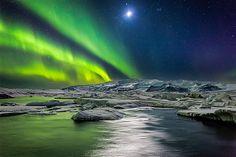 Aurora Boreal e lua iluminam o céu e os iceberg da lagoa glacial Jokulsarlon, na Islândia