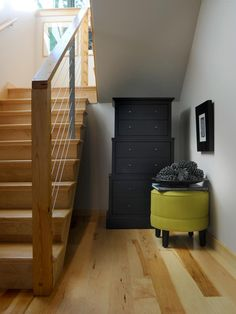 """An alcove below the staircase offers additional storage space as well as a spot to make a subtle design statement.""""I think with a family room, you are going to accrue a lot of junk: games and people's stuff,"""" says interior designer Linda Woodrum. """"It is a great way to do storage."""""""