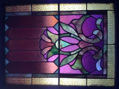 A stained glass window hanging in the front space of RED 7 SALON Evanston.