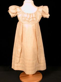 Childs dress - Unbleached calico, high waist, short puffed sleeves. Centre front panel has penwork embroidery, flounce around neck and down either side of panel, also down skirt, hand edging stitched. Five tucks around bottom of skirt. 1820 (circa)