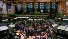 A busy stock trading room, full of people standing on front of a multitude of computer screens - Enron scandal