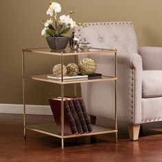 Bring the roaring '20s to life with this opulently simple side table. The minimalist architecture contrasts with the luxurious, metallic gold frame, high shine mirrored shelf, and sleek glass tabletop to create a vision à la Gatsby. Use the shelves to
