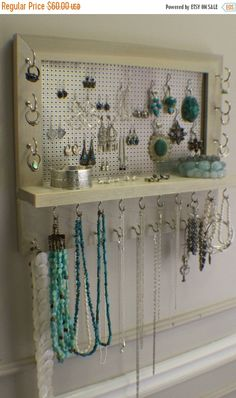 ****This is a MADE TO ORDER listing. You will receive a jewelry organizer the same as the one pictured above but this one already has a home.***** This listing is for a wall mounted jewelry organizer just like the one pictured above. There is plenty of room for all you jewelry storage needs. It is stained a beautiful weathered grey color. Its very durable and will last for years. The shelf on the front is large enough for any additional jewelry you dont want to hang from any of the many…