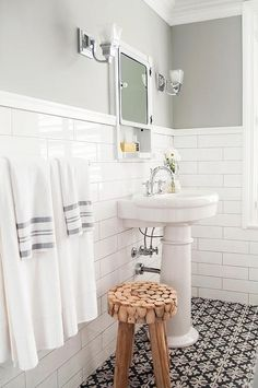 Gorgeous bathroom features upper walls painted gray, Sherwin Williams Gray Clouds, and lower walls clad in white brick tiles lined with an oval pedestal sink fitted with a gooseneck faucet under a white metal inset medicine cabinet with shelf alongside a black and white tiled floor by StonePeak Tiles.