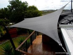 Shade sail attached to roof and corner of the deck.
