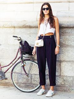 A white bank top is paired with a coordinating pinstripe suit and Nike sneakers
