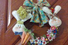 Confeccionada pela artesã Alina Nowacki Moura, esta guirlanda com arco de palha tem coelhinhos em algodão cru, arrematada por cenouras em tecido e flores de fuxico com miolo de botão também forrado em tecido. Com 28cm de diâmetro, a peça enfeita a porta, dando as boas-vindas aos visitantes
