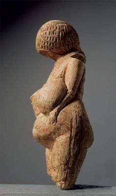 Venus figurine from Kostenki  | 23 000 - 21 000 BC. Limestone    H 10.2 cm.   This figurine represents the Palaeolithic 'Venus', with overlarge breasts and belly. The faceless head bends towards the chest while the arms are pressed to the body with hands on the belly. Covering the surface of the head are rows of incisions indicating a hair style or cap. Relief work in the form of a tight plait convey a breast ornament tied up at the back. There are bracelets on the arms.