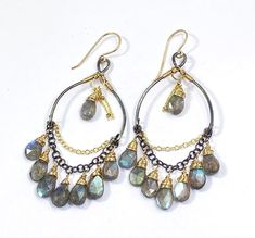 Amazing, strong blue flash labradorite briolettes dangle and show off their colors on these mixed metal boho chandelier hoop earrings! Oxidized and polished, sterling silver hand forged wires dangle chains of gold fill and oxi sterling silver to dangle these mesmerizing briolettes, wrapped in yards of 14 kt gold filled wires. Centering the hoops are more briolettes, wrapped in gold filled wires and dangling gold filled studded chains. These are so pretty you can't look away from them when…