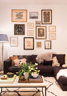 Vintage effect gallery wall with souk wool rug and furs on corner sofa. By Banda Property. © Phil Durrant photography
