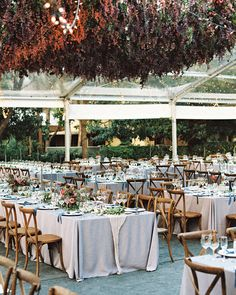 "A Gem-Toned Texas Wedding with French Touches | Martha Stewart Weddings - Silver dupioni linens were flipped over to showcase a lavender undertone when dressing the tables in the tent, which were finished off with gauzy gray runners. ""Instead of having flowers on the table, why not top to have them on the ceiling,"" the bride explains of the tent's focal point. ""There's something quite romantic about being surrounded by flowers and greenery."""