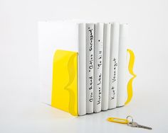 """Stricking yellow color bookends. Minimalist and contemporary bookends to keep your space organized. Yellow color. Modern and minimalistic design would emphasize the value of what is in between.  One piece measures 5""""9 by 4""""3 with base 4""""72 in (15 by 11 ..."""