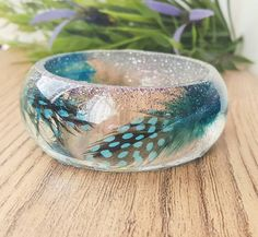 Check out this item in my Etsy shop https://www.etsy.com/uk/listing/510077402/teal-feather-bangle-boho-feather-jewelry