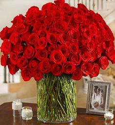 """100 Premium Long Stem Red Roses in a Vase How much do you love them? Count the ways from 1 to 100 with this lush and luxurious bouquet of 100 romantic premium long-stem red roses. The ultimate """"I love"""