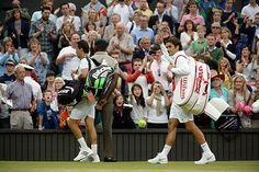 Roger Federer and Santiago Giraldo walk off Centre Court