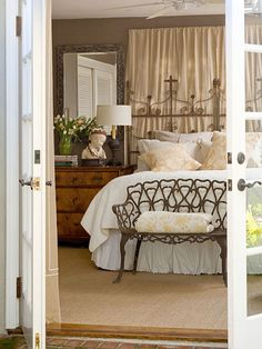 A pair of salvaged monastery beds form a dramatic headboard. The linen curtains hung behind the headboard add a casual touch to the scene and hide the room's window. An ornate wrought-iron bench sits at the foot of the bed and serves as a catchall for extra blankets. Natural elements, such as the wood dresser-turned-nightstand and sisal rug, add a casual touch to the room's elegant accents.