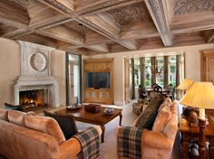 Family room with box beamed hand-painted ceiling, fireplace, media cabinetry, and surround sound.