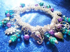 'Indian Summer' charm bracelet.......beautiful jewelled elephants, ethnic sun symbols, peace signs & rainbow haematite hearts with rich emerald & amethyst coloured crystal & glass beads........available at www.facebook.com/RetroBling