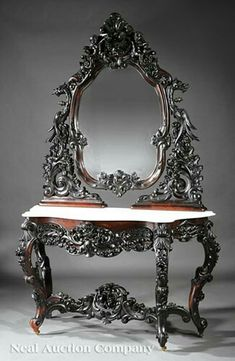 Rare American Rococo Highly Carved Rosewood Dressing Table, mid-19th c., New York, possibly Alexander Roux, arched crest, fruit and flower cartouche flanked by putti, mythological bird supports, shield shaped mirror centered by a cabochon, serpentine carrara marble top, conforming drawer, C scrolled fruit carved cabriole legs connected by a foliate and floral stretcher, h. 85 in., w. 53 1/2 in., d. 21 7/8 in.