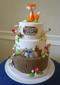 A 3 tier, 3 flavoured sponge with woodland creatures, cute toadstools, wired flowers, gumpaste fox topper and name plaque all handmade.