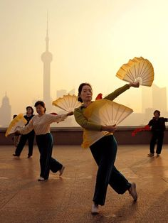Morning Exercise, Shanghai - Early risers perform traditional morning exercises on the Bund, Shanghai's famous riverfront boulevard. Stretching and low-impact exercise have been staples in Chinese culture for centuries. - Photograph by Justin Guariglia