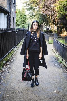 Anisa Sojka wearing MIOPO black jewelled jumper, The Fold black trousers, EILEEN FISHER black coat, TUSTING black and red bag, Seven Boot Lane black ankle boot, LAYANA London multi-colored earrings, and stackable iLoveDesigner bracelets. Street style shot in London by Push PR.
