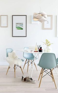 bright dining room with white walls, light wood floor, and mid century modern furntiure