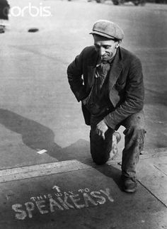 A man kneeling on the pavement, next to a sign showing the way to a speakeasy, during the Prohibition in America. Photo by Hulton Archive/Getty Images - Photo by Hulton Archive/Getty Images