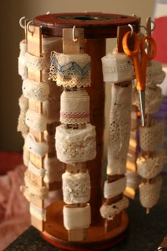 using a big antique bobbin to hang the vintage ribbons. Just screw in the hooks and find some paint sticks.