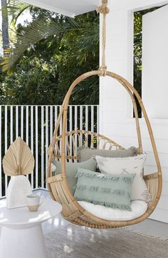A modern coastal luxury / beachy boho outdoor space with cane hanging chair by Sea Tribe