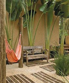 Plantas tropicais e moveis rústicos deixam  o redário charmoso.