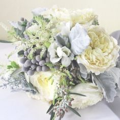 9 different flowers in the bridal bouquet from a white, silver, red and orange wedding in NYC.