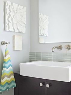 Small baths need smart solutions. On-the-wall space savers include a frameless mirror, a single-handle faucet, and a towel hook instead of a bar. A pale blue-gray paint color keeps the room light, while bright accent colors bring energy.