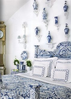 Blue and white Delft on wall brackets, blue and white upholstered bed, linens - Carolyne Roehm
