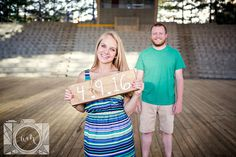 Holding wooden sign engagement picture at Worlds Fair Site by Amanda May Photos